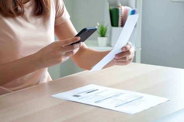 Kobieta używa smartfona do zeskanowania kodu kreskowego, aby płacić miesięczne rachunki telefoniczne po otrzymaniu faktury wysłanej do domu. koncepcja płatności rachunków online