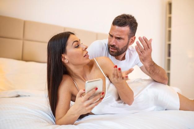 Kobieta używa smartfona, spróbuj wyjaśnić zazdrość, zły mąż, że nie ma innego mężczyzny, który wskazuje ekran ręki, czuje się zdezorientowana.