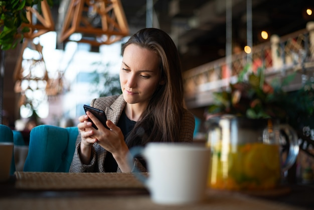Kobieta używa smartfona w ręce przy stole w restauracji