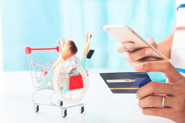 Kobieta używa smartphone i kredytowej karty zakupy piękna rzeczy. zakupy online, e-płatności