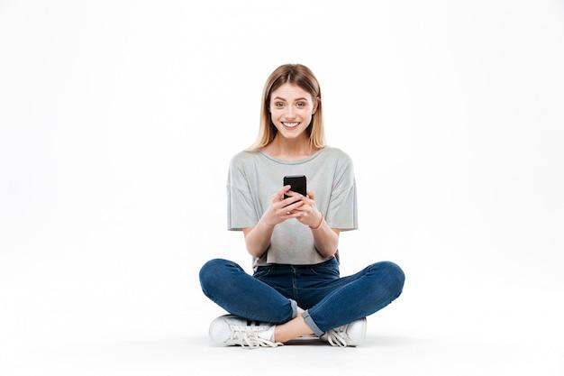 Kobieta używa smartphone i obsiadanie na podłoga