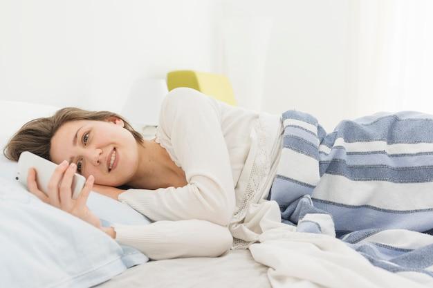 Kobieta używa smartphone podczas gdy w łóżku