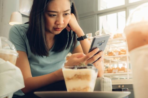 Kobieta używa smartphone w piekarni kawiarni.