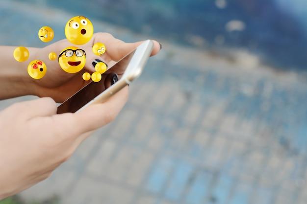 Kobieta używa smartphone wysyłania emoji.