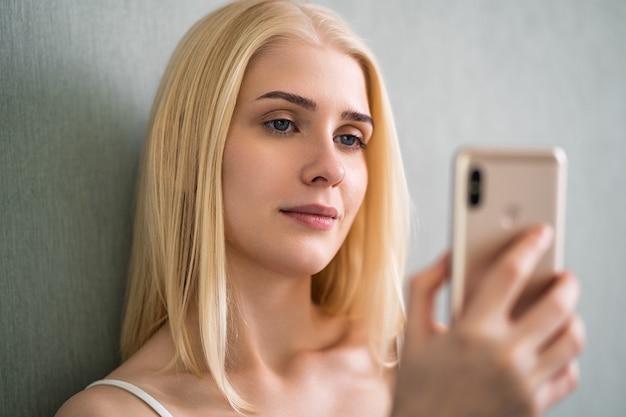 Kobieta używa swojego smartfona, uśmiechając się, leżąc na łóżku.