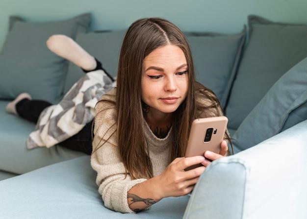 Kobieta używa swojego smartfona w domu podczas pandemii