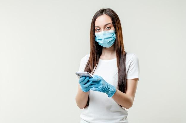 Kobieta używa telefon jest ubranym maskę i rękawiczki