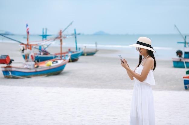 Kobieta używa telefon komórkowego na plaży
