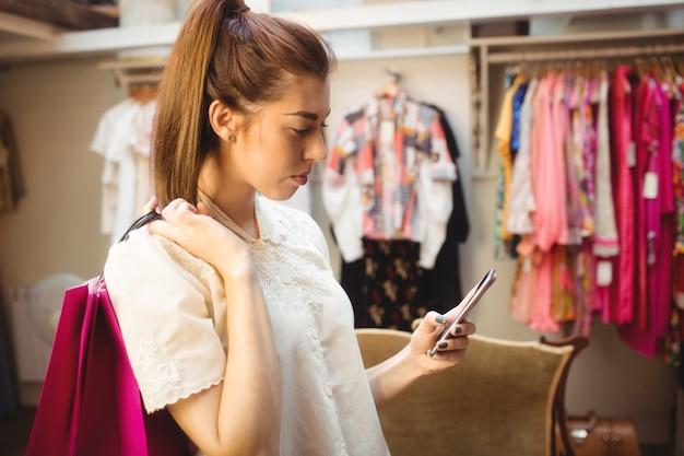 Kobieta używa telefon komórkowego podczas gdy robiący zakupy