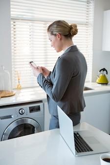 Kobieta używa telefon komórkowego w kuchni