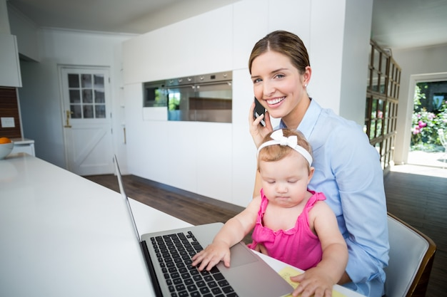 Kobieta używa telefon komórkowego z dziewczynką laptopem