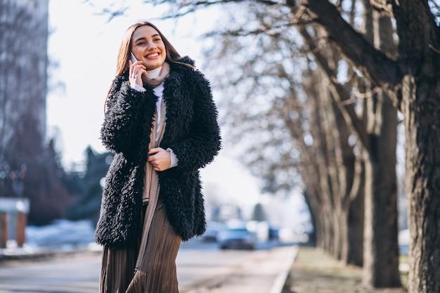 Kobieta używa telefon na zewnątrz sthe ulicy