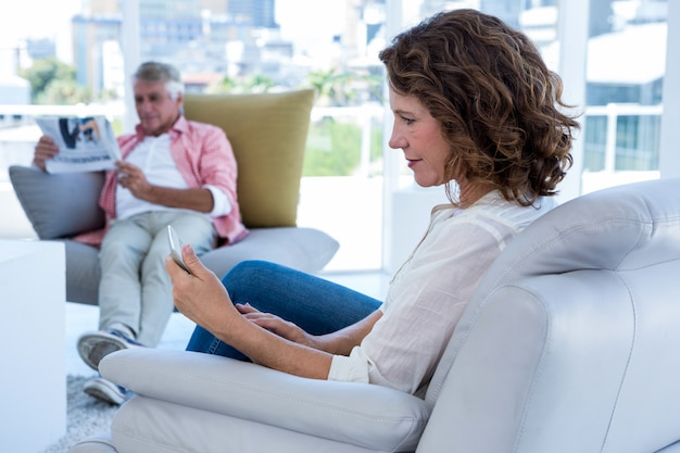 Kobieta używa telefon podczas gdy mężczyzna czyta gazetę