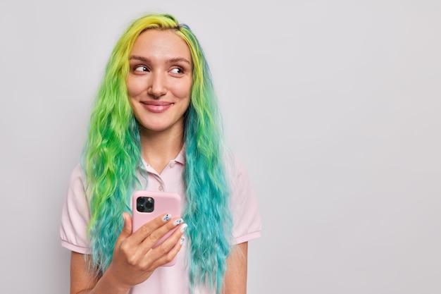 Kobieta używa telefonu komórkowego do rozmów online ma długie, kolorowe włosy, korzysta z wiadomości w aplikacji lub robi zakupy, ubrana swobodnie, odizolowana na szaro