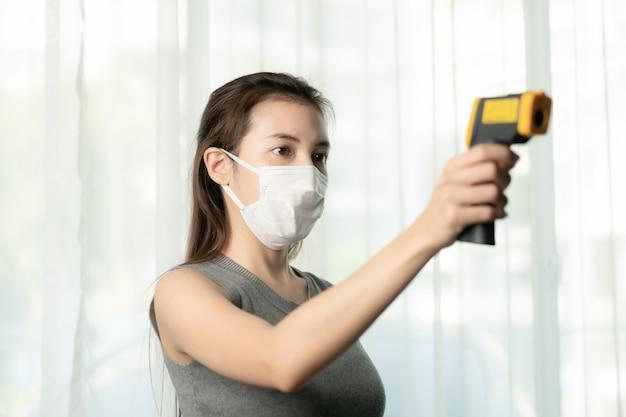 Kobieta używa termometru, aby sprawdzić ludzi pod kątem ochrony przed wirusem koronowym. użyj termometru cyfrowego do sprawdzania temperatury.