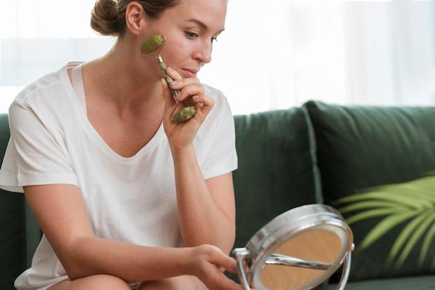 Kobieta używa twarz masażu narzędzia jaźni opieki pojęcie