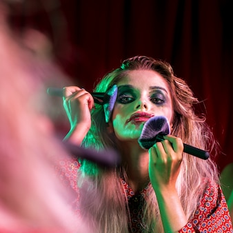 Kobieta używa wielokrotność muśnięcia na jej twarzy