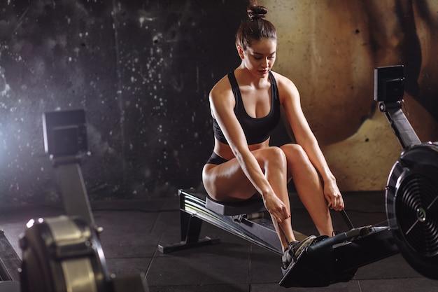 Kobieta używa wioślarską maszynę w gym. kobieta robi trening cardio w klubie fitness.