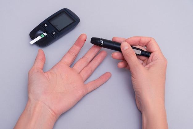 Kobieta używa wykrywacza glukozy we krwi