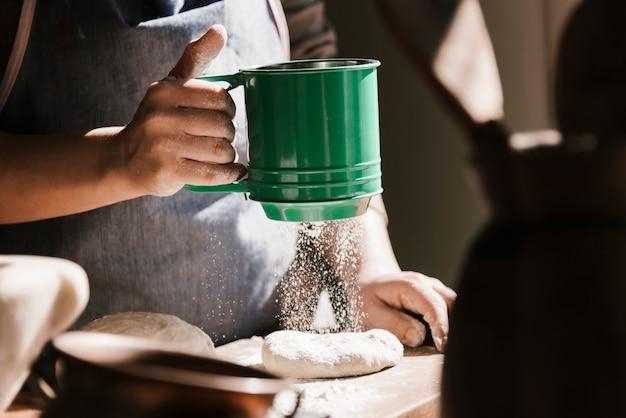 Kobieta używa zielonego mąki sito