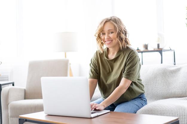 Kobieta używać komputera przenośnego siedząc kanapa tło dużego okna wnętrze domu samica niezależna pracująca w domu