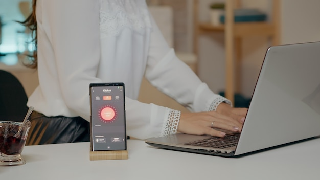 Kobieta używająca asystenta głosowego kontrolującego światło włączające go it