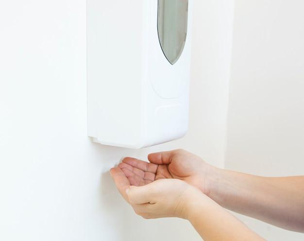 Kobieta używająca automatycznego dozownika środka dezynfekującego do rąk w miejscu publicznym