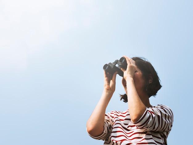 Kobieta używająca lornetki bada poszukiwania