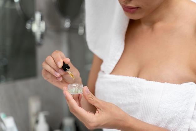 Kobieta używająca olejku do twarzy z zakraplaczem