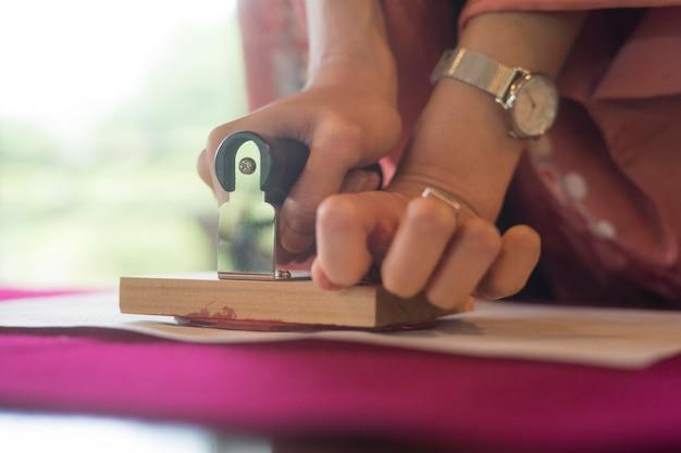 Kobieta używająca pieczątki na papierze origami