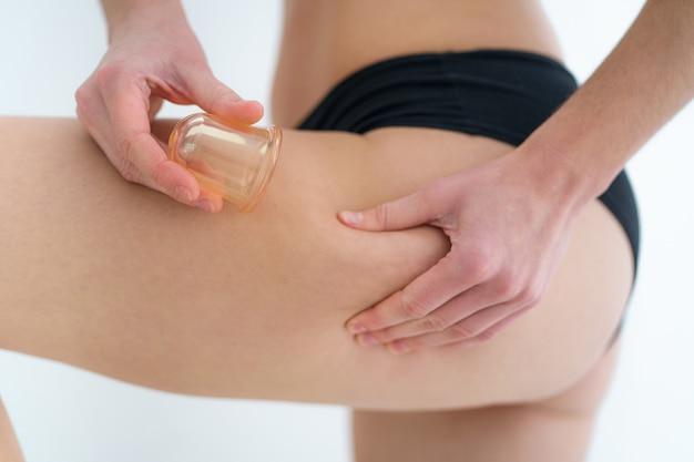 Kobieta używająca próżniowych słoików do masażu do masowania skóry pośladków i pośladków w celu zapobiegania i leczenia cellulitu, rozstępów i problemów z ciałem po prysznicu w domu. zdrowie skóry