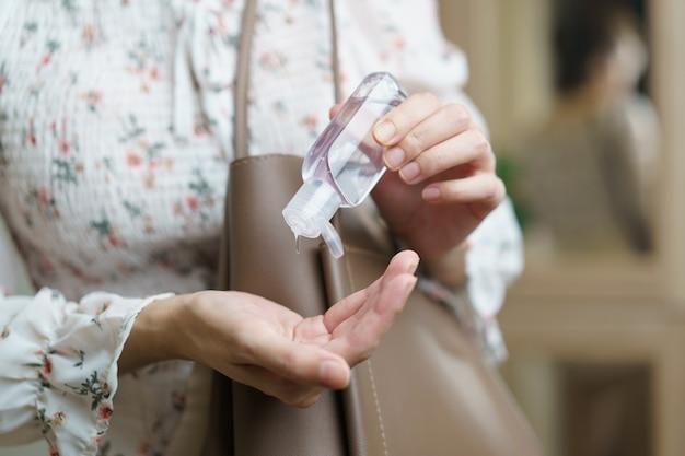 Kobieta używająca sprayu do dezynfekcji rąk z torebki, zapobieganie koronawirusowi.