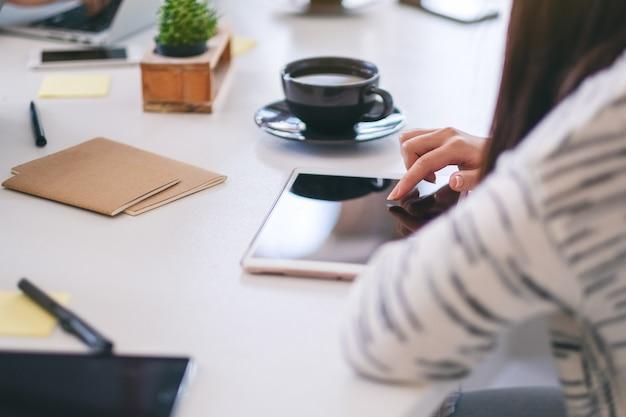 Kobieta używająca tabletu i wskazująca palcem na tablecie z filiżanką kawy na stole
