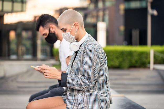 Kobieta używająca telefonu komórkowego podczas pandemii covid-19, koncepcji dystansu społecznego, technologii i wirusa koronowego.