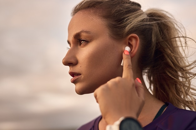 Kobieta używająca wkładek dousznych podczas treningu na świeżym powietrzu