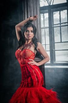 Kobieta vintage czerwona sukienka stary zamek piękna księżniczka w uwodzicielskiej sukience elegancka biała kobieta bajkowa historia w pobliżu dużego okna z dymną mgłą