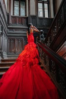 Kobieta vintage czerwona sukienka stary zamek piękna księżniczka w uwodzicielskiej sukni elegancka kobieta kaukaska bajka ciemne schody