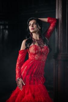 Kobieta vintage czerwona sukienka stary zamek piękna księżniczka w uwodzicielskiej sukni elegancka kobieta kaukaska bajkowa historia