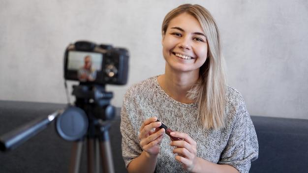 Kobieta vlogger pokazująca szminkę. blogerka kosmetyczna filmująca codzienny samouczek dotyczący rutynowego makijażu w pobliżu aparatu na statywie