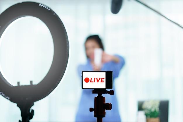Kobieta vlogger trzyma w rękach pielęgnację skóry, patrzeje w kamerze podczas gdy nagrywający wideo dla blogu. relacja na żywo