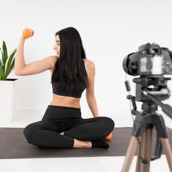 Kobieta vlogger w domu z ciężarami ćwiczeń