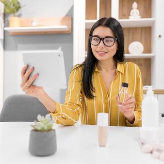 Kobieta vlogger w domu z tabletem i polecanymi produktami
