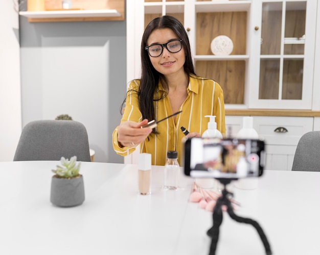 Kobieta vlogger w domu ze smartfonem i polecanymi produktami