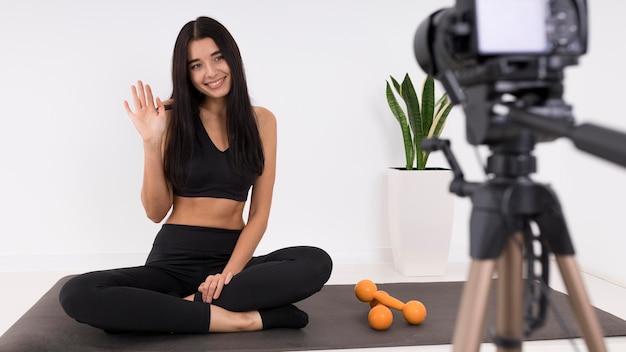 Kobieta vlogging w domu z aparatem podczas ćwiczeń