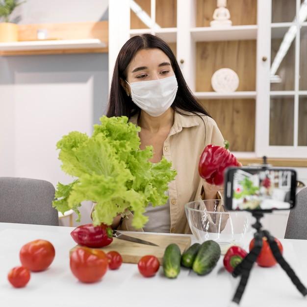 Kobieta vlogging w domu z medyczną maską i warzywami