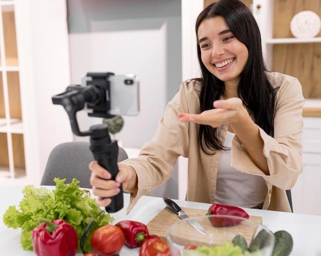 Kobieta vlogging w domu ze smartfonem i warzywami