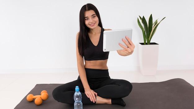 Kobieta vlogowanie w domu podczas ćwiczeń z tabletem