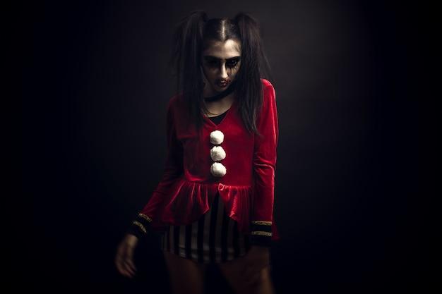 Kobieta w aksamitnym czerwonym kostiumie i przerażającym makijażu na twarzy stoi