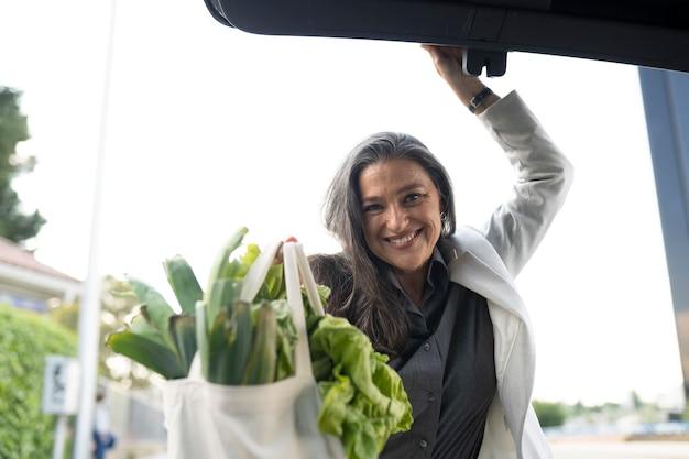Kobieta w bagażniku samochodu z zakupem
