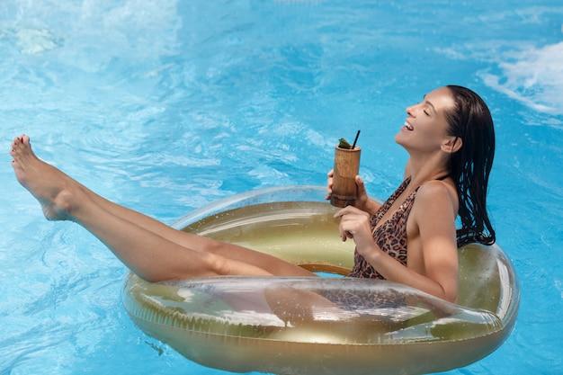 Kobieta w basenie na gumowym pierścieniu, relaksując się podczas wakacji, ciesząc się sezonem letnim, spędzając czas pijąc świeże bavereges, ubrana w kostium kąpielowy, pozuje z mokrymi włosami. koncepcja rekreacji.